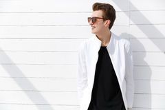 Smiling young man in sunglasses over white wall background Stock Photography