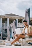 Smiling young man in sunglasses sitting on chaise longue. And using laptop royalty free stock image