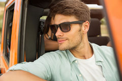 Smiling young man in sunglasses sitting on a front seat Royalty Free Stock Photos