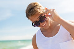 Smiling young man in sunglasses on summer beach. Summer holidays and people concept - happy smiling young man in sunglasses on beach Stock Photography