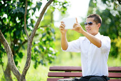 Smiling young man in sunglasses taking selfie through tablet Royalty Free Stock Photography