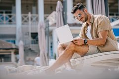 Smiling young man in sunglasses using laptop while resting on chaise. Longue royalty free stock images