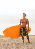 Smiling young man with surfboard on beach Royalty Free Stock Images