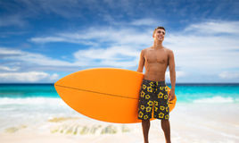 Smiling young man with surfboard on beach. Summer vacation, people and water sport concept - smiling young man with surfboard or stand up paddle board on beach Stock Photography