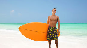 Smiling young man with surfboard on beach. Summer vacation, people and water sport concept - smiling young man with surfboard or stand up paddle board on beach Stock Photos