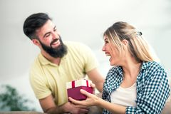 Smiling young man surprising cheerful woman with a gift box. Smiling young men surprising cheerful women with a gift box at home Royalty Free Stock Photography