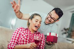 Smiling young man surprising cheerful woman with a gift box. Smiling young men surprising cheerful women with a gift box at home Stock Images