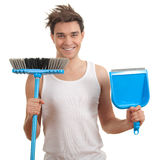 Smiling young man with sweeping brush Royalty Free Stock Photos