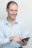 Smiling young man with tablet computer on white background Royalty Free Stock Images