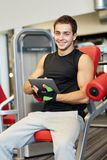 Smiling young man with tablet pc computer in gym Royalty Free Stock Photography