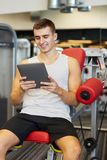 Smiling young man with tablet pc computer in gym Stock Image