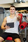 Smiling young man with tablet pc computer in gym Royalty Free Stock Image