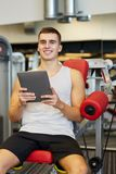 Smiling young man with tablet pc computer in gym Royalty Free Stock Images