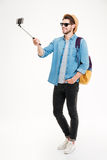 Smiling young man taking photos with smartphone and selfie stick. Full length of smiling young man with backpack taking photos with smartphone and selfie stick Stock Photos