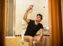 Smiling young man taking selfie while defecating Royalty Free Stock Images