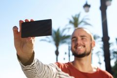 Smiling young man taking a selfie with his mobile phone Stock Image