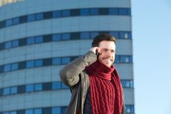 Smiling young man talking on cellphone in the city Royalty Free Stock Image