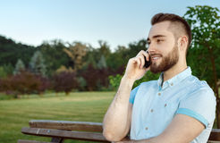 Smiling young man talking on the cellphone Stock Images