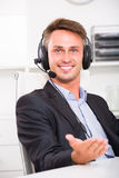 Smiling young man talking on headset at office. Smiling young man talking on headset at company office Royalty Free Stock Photography