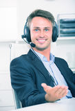 Smiling young man talking on headset at office. Smiling young man talking on headset at company office Stock Image
