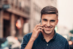 Smiling young man talking on his cellphone in the city Royalty Free Stock Photography