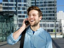 Smiling young man talking on mobile phone at airport Stock Images