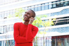 Smiling young man talking on mobile phone in the city Stock Photography