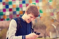 Smiling young man talking on mobile phone in a city .Young smiling student outdoors talking on cell smart phone.Life style.City stock image
