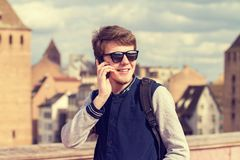 Smiling young man talking on mobile phone in a city .Young smiling student outdoors talking on cell smart phone.Life style.City royalty free stock photo