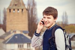 Smiling young man talking on mobile phone in a city .Young smiling student outdoors talking on cell smart phone.Life style.City stock photos