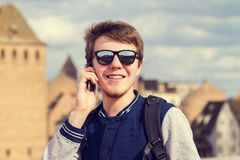 Smiling young man talking on mobile phone in a city .Young smiling student outdoors talking on cell smart phone.Life style.City royalty free stock photos