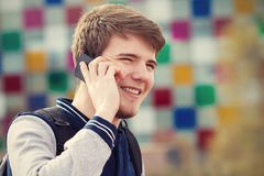 Smiling young man talking on mobile phone in a city .Young smiling student outdoors talking on cell smart phone.Life style.City royalty free stock image
