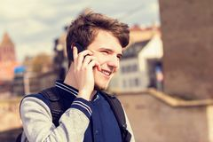 Smiling young man talking on mobile phone in a city .Young smiling student outdoors talking on cell smart phone.Life style.City royalty free stock images