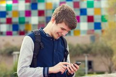 Smiling young man talking on mobile phone in a city .Young smiling student outdoors talking on cell smart phone.Life style.City royalty free stock photography