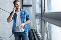 Smiling young man talking on mobile phone, looking at the window at home. Smiling young man talking on mobile phone, looking at the window at home stock photography