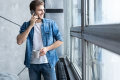 Smiling young man talking on mobile phone, looking at the window at home. Smiling young man talking on mobile phone, looking at the window at home royalty free stock image