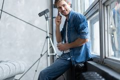 Smiling young man talking on mobile phone, looking at the window at home. Smiling young man talking on mobile phone, looking at the window at home stock photo