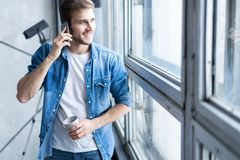 Smiling young man talking on mobile phone, looking at the window at home. Smiling young man talking on mobile phone, looking at the window at home royalty free stock photography