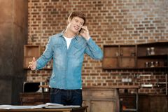 Smiling young man talking on the phone with boss. Great news. Cheerful young man standing near the table and talking on the phone while receiving pleasant news Royalty Free Stock Images