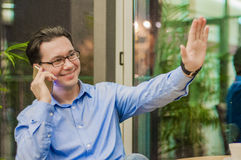 Smiling young man talking on the phone and showing greeting gesture. Stock Photos