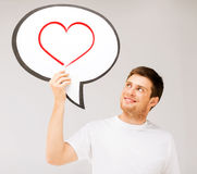 Smiling young man with text bubble and heart in it Stock Image