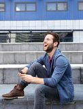 Smiling young man text messaging on cellphone Stock Photo