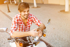 Smiling young man texting on the cellphone. While sitting on a scooter on a summer day Stock Photos