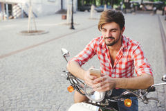 Smiling young man texting on the cellphone. While sitting on a scooter on a summer day Royalty Free Stock Photos