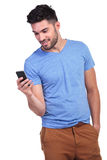 Smiling young man texting on his smartphone. Smiling young man reading or writing a text message on his smartphone Stock Photography