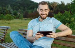 Smiling young man texting on the tablet Stock Photo
