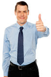 Smiling young man with thumbs up gesture. Business concept Royalty Free Stock Image
