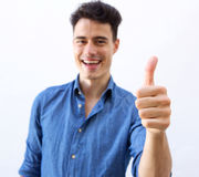 Smiling young man with thumbs up hand sign Royalty Free Stock Images