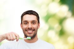 Smiling young man with toothbrush Stock Photo