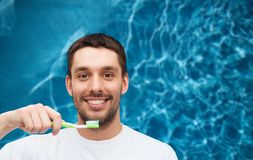 Smiling young man with toothbrush Stock Images